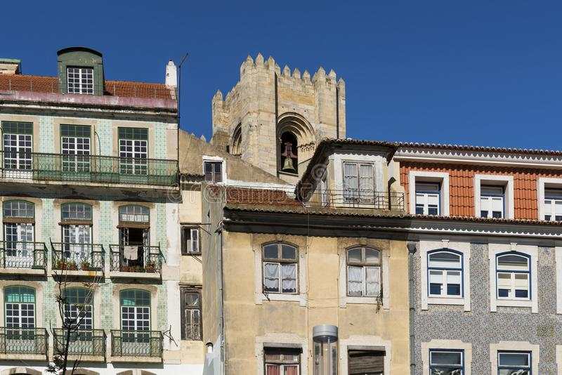 Detail of the facade of traditional buildings with the bell tower of the Lisbon Cathedral on the background in Lisbon, Portugal stock photography