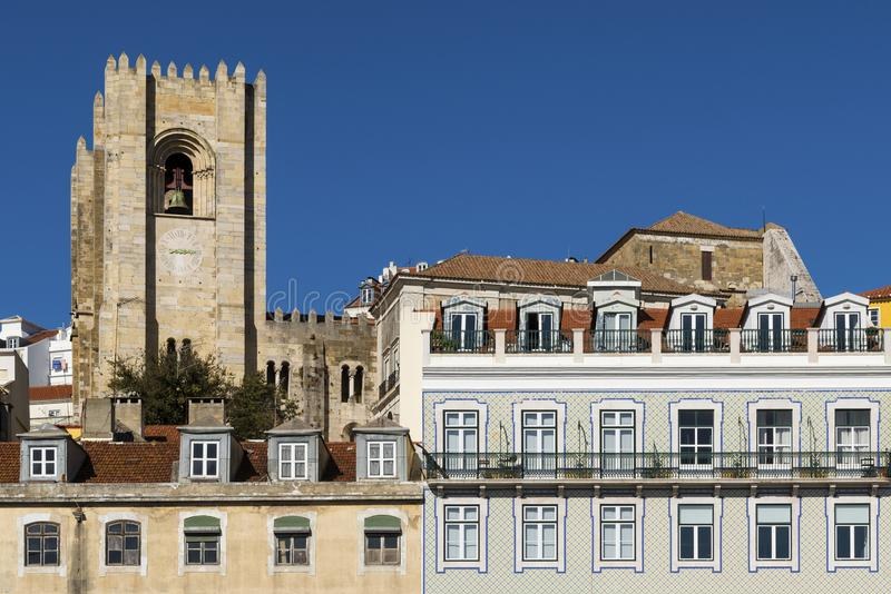Detail of the facade of traditional buildings with the bell tower of the Lisbon Cathedral on the background in Lisbon, Portugal royalty free stock photography