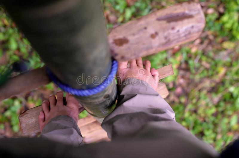 Detail of Feet Standing On a Bamboo Ladder royalty free stock photography