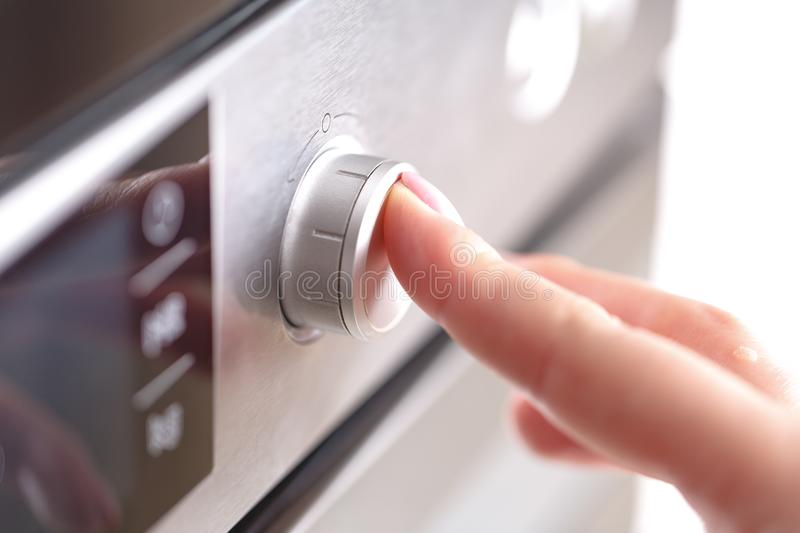 Detail of female hand while using the microwave stock photos