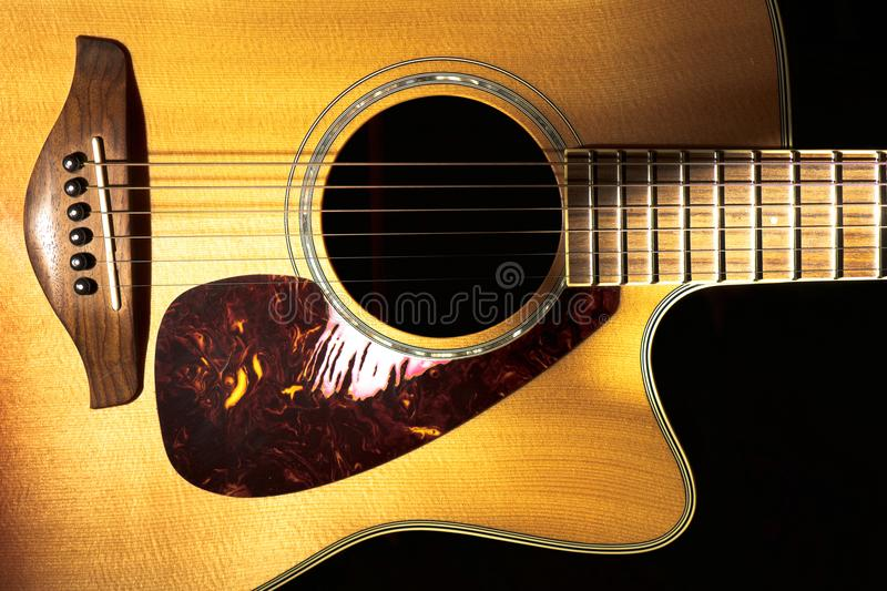Detail of folk acoustic guitar on a black background stock photo