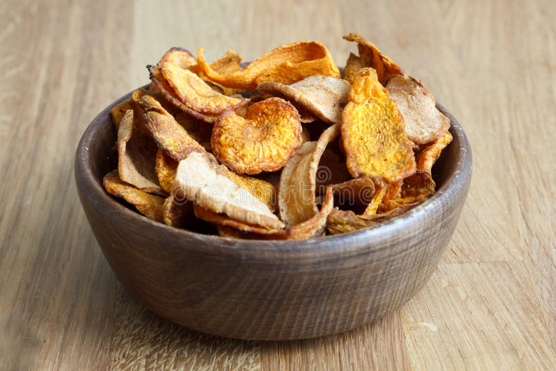 Detail of fried carrot and parsnip chips in rustic wood bowl. stock photo