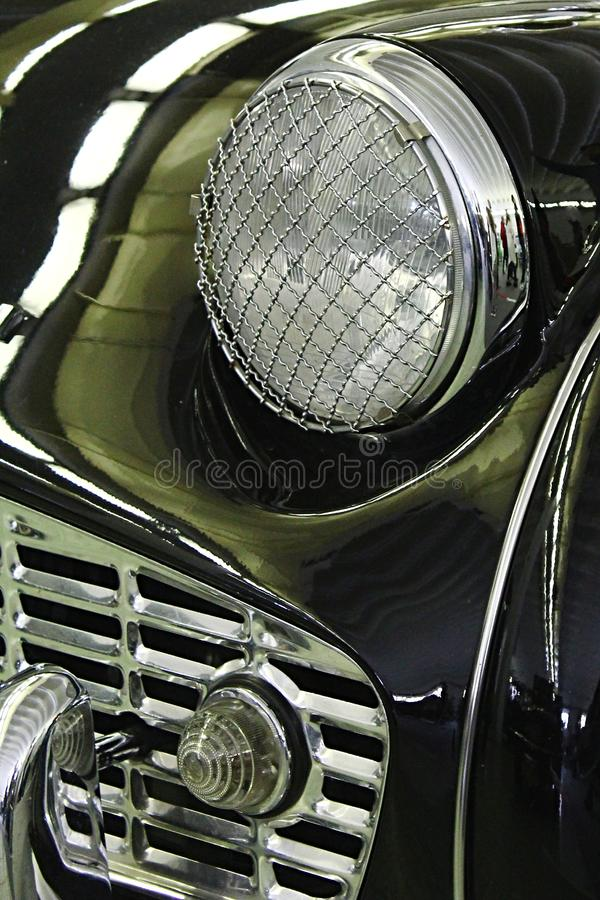 Detail of front mask and headlight with steel cage protection of vintage british sports car roadster. From years 1955-1962 stock images