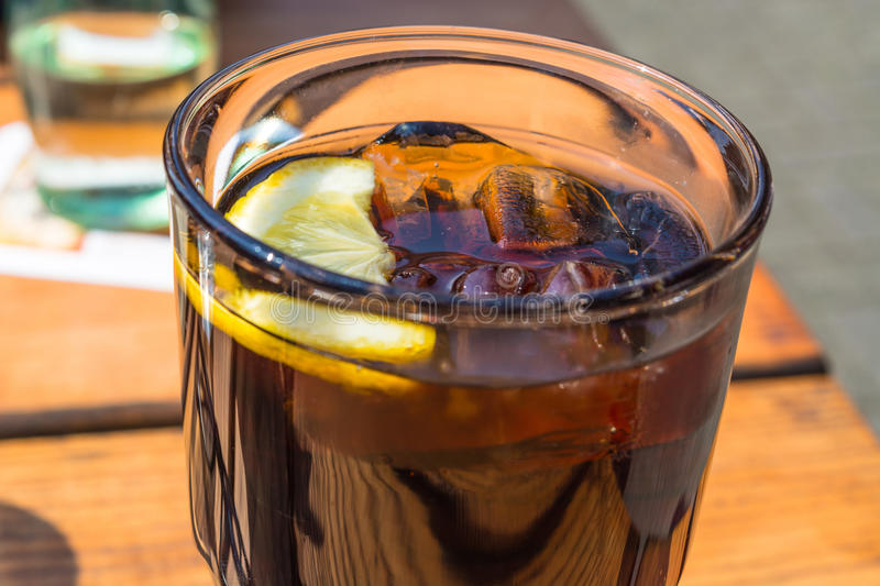 Detail, glass of cola with ice and lemon. On a wooden table royalty free stock photos