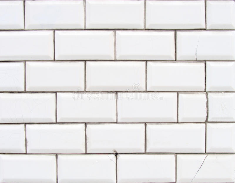 Detail of a glossy white beveled tile wall with damage. Detail of a glossy white beveled tiled wall with damage stock photography