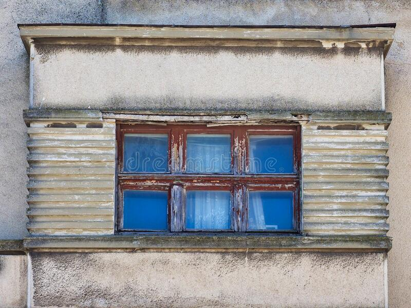 Detail of Grey Concrete Building With Blue Windows. Detail of the grey pollution stained concrete facade of an older style building with a grid of wood framed stock photo
