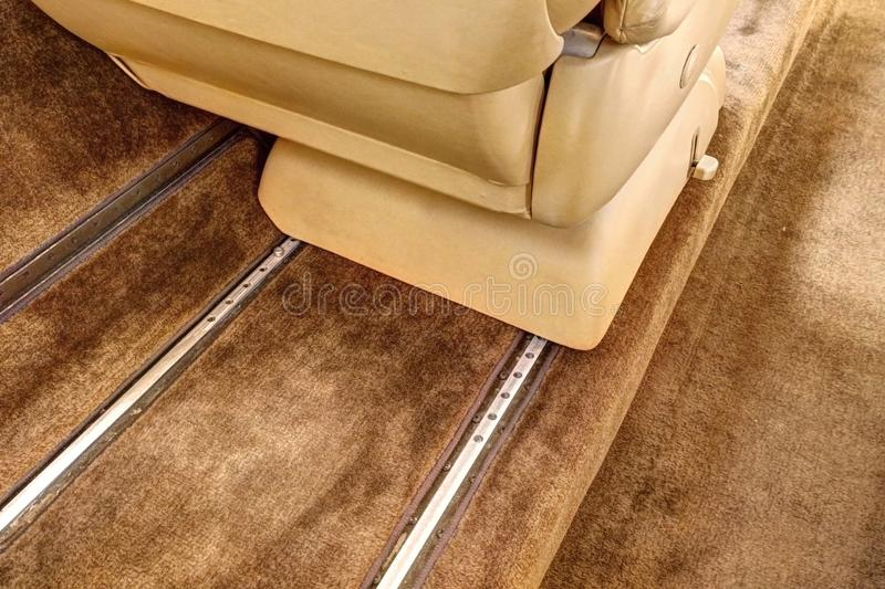 Detail of guiding rails of aircraft leather chair with brown carpet royalty free stock images