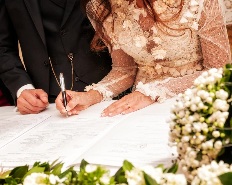 Hands signing during the wedding. Detail of the hand of a bride who signs the marriage act royalty free stock images
