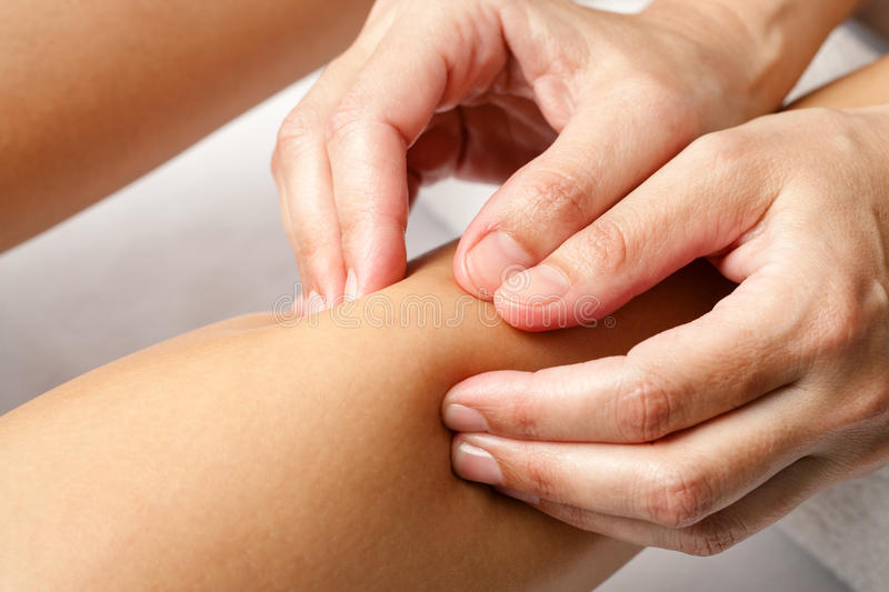 Detail of hands doing osteopathic massage on female calf muscle. Macro close up of hands doing rehabilitation massage on female calf muscle stock photo