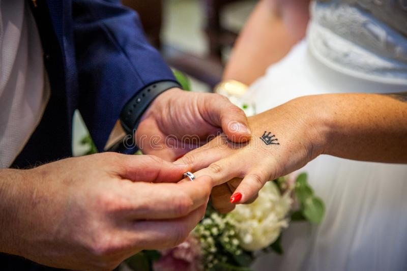 Detail of the hands of a groom putting the ring on the finger of the hand of the bride royalty free stock image