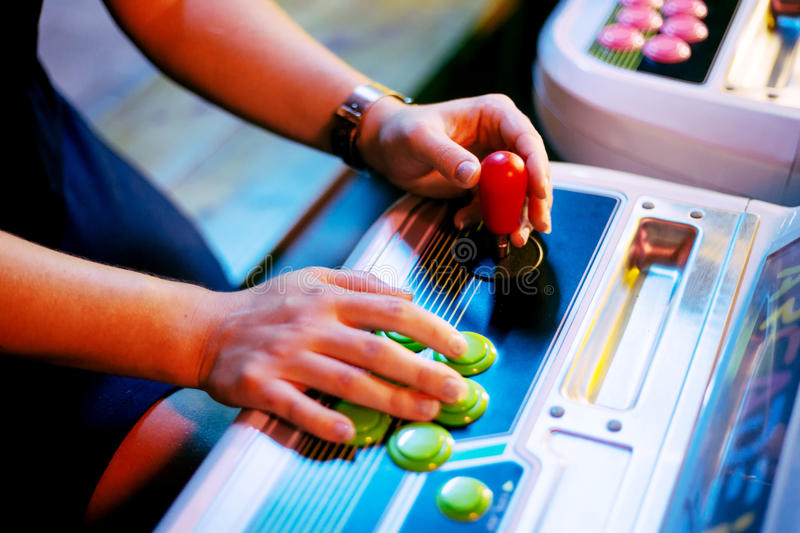 Detail on hands holding joystick and pushing buttons in a gaming room. Detail on hands holding joystick and pushing buttons, playing an old arcade video game stock photos