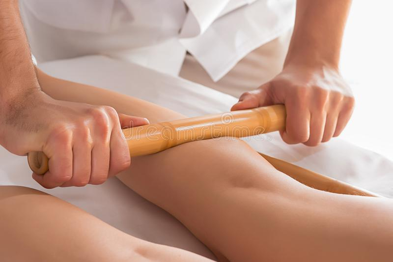 Detail of hands massaging human calf muscle. Therapist applying pressure on female leg stock photography