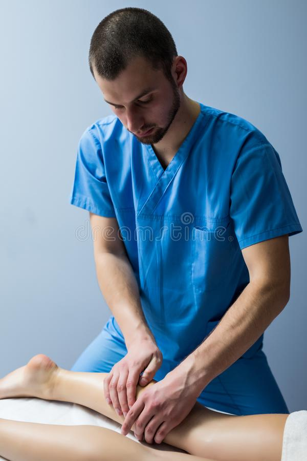 Detail of hands massaging human calf muscle. ManTherapist applying pressure on female leg. Detail of hands massaging human calf muscle.Therapist applying royalty free stock photo