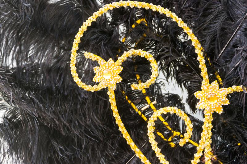 Detail of the helmet with feathers and embroidery for the carnival. Black feathers and golden embroidery of the backs for the carnival stock photo