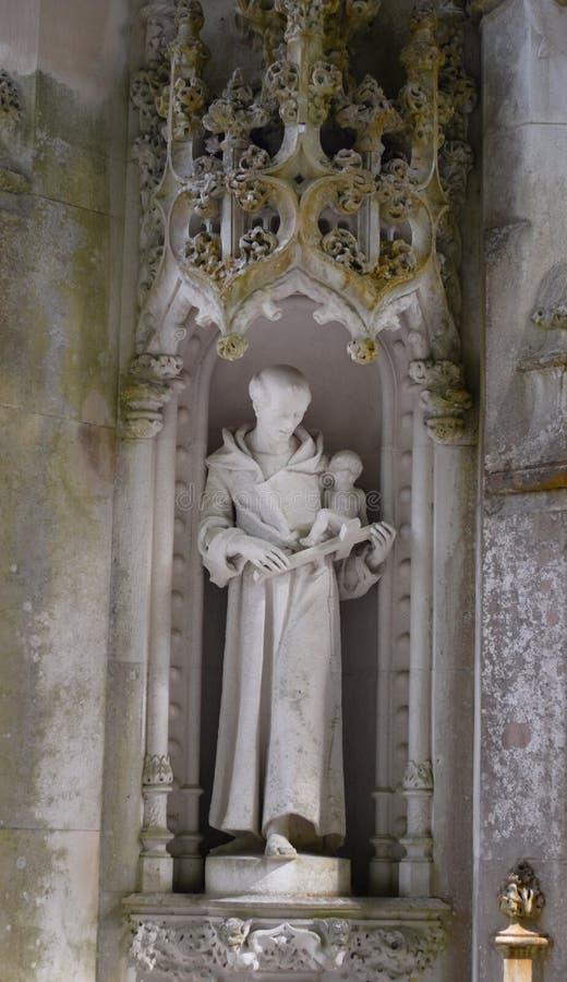 Detail in het park - oud steenstandbeeld van monnik met kruis en baby, Quinta da Regaleira in Sintra, Portugal stock afbeeldingen
