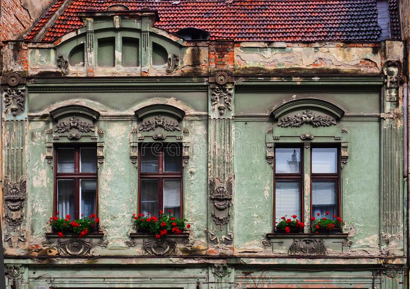 Historic Green House, Brasov, Romania. Detail of an historic pale forest green house with red flowers in window boxes, Brasov, Romania royalty free stock photos