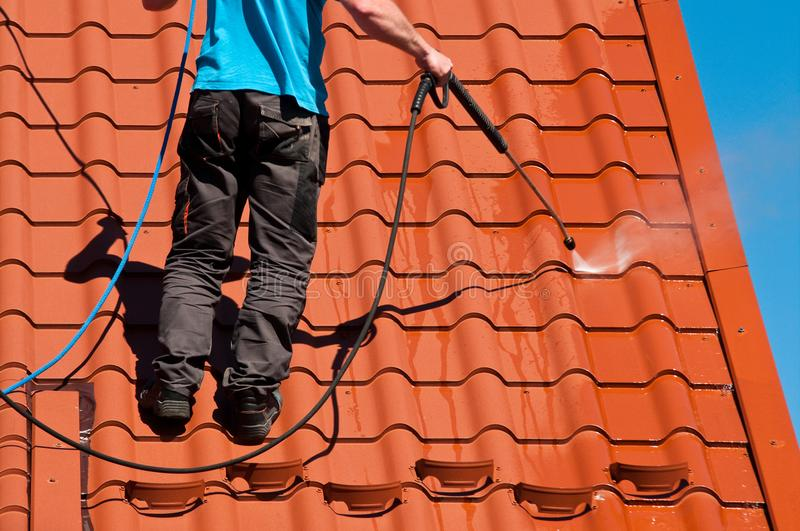 Worker cleaning metal roof with high pressure water. Detail of house maintenance: a worker cleaning metal roof with high pressure cleaner royalty free stock image