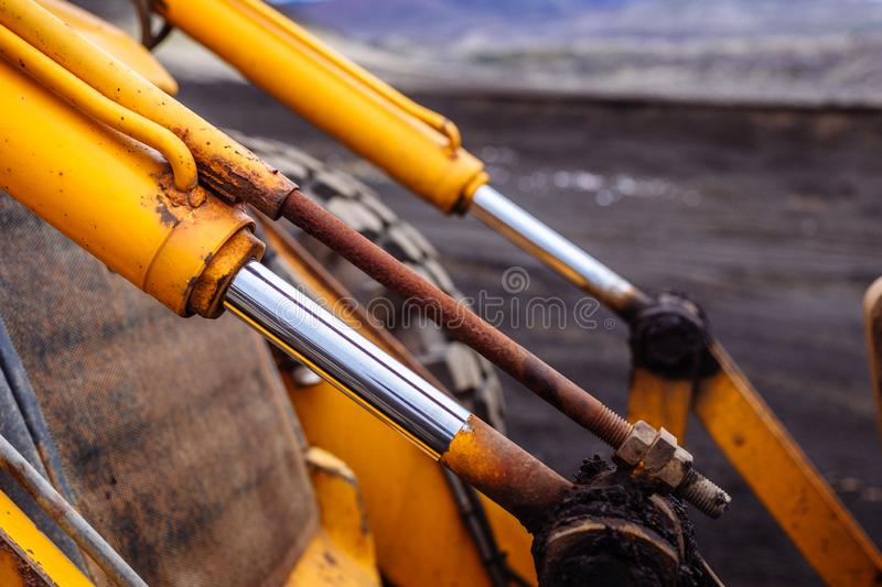 Detail on hydraulic digger of yellow heavy duty digger excavator stock image