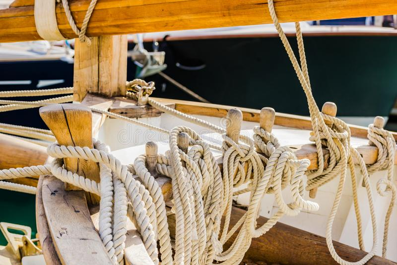 Yachting, wooden classical sailing boat, close-up of tied nautical ropes on wood cleats. Detail image of moored ropes on wooden cleats on old sailboat royalty free stock photography