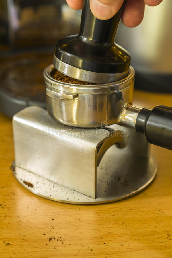 Detail image of tamping espresso grounds into a bayonet royalty free stock photography