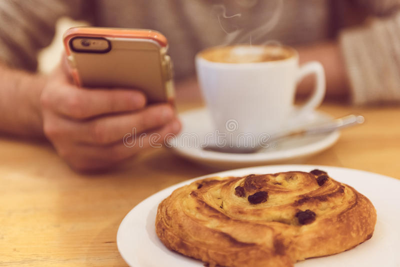 Detail image of unrecognisable man drinking coffee and holding smart phone while having breakfast in restaurant. stock photography