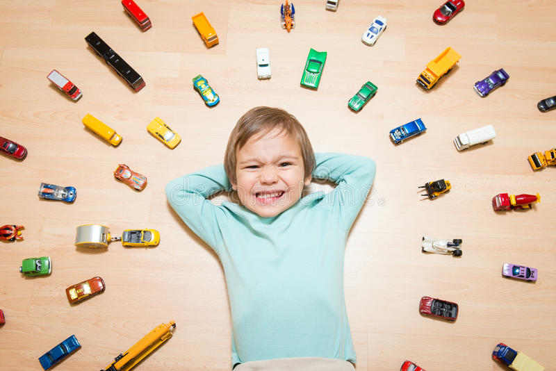 Detail of kid with toy cars around him. Adorable boy lying on the ground with toy cars around stock image
