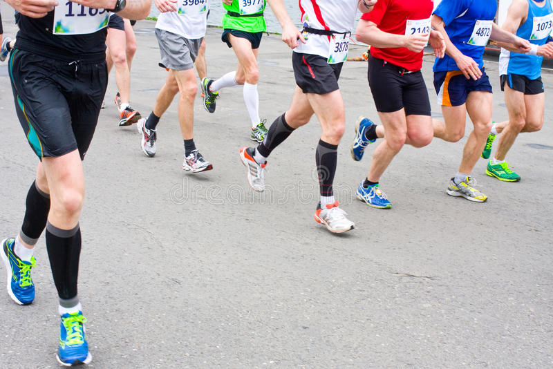 Detail of the legs of runners at the start of a marathon race royalty free stock images