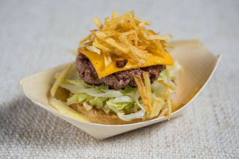 Detail of a little hamburger with lettuce cheese and chips stock image