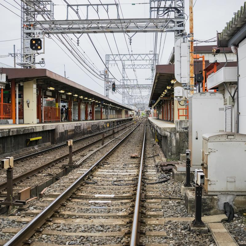 Detail of local railway station in Kyoto, Japan. Detail of local railway station with contact lines, traffic signals and rails in Kyoto, Japan. Urban railroad stock images