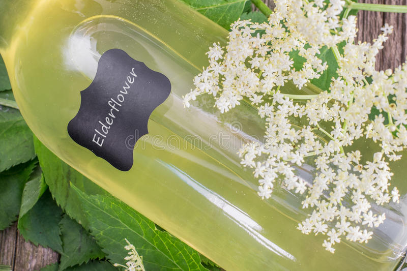 Detail of a Lying Bottle of Elderflower Syrup with Elderflower. On Old Wooden Table royalty free stock images