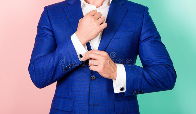 Detail make outfit elegant. Male fashion. Perfect to last detail. Male hand check button on shirt sleeve. Cufflinks. Match with luxury classic suit jacket. Make stock photography