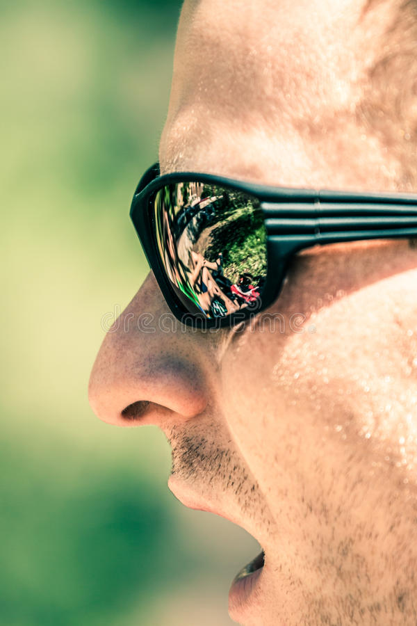 Detail of man face in sport sunglasses. Detail of man face with open mouth wearing sport sunglasses stock image