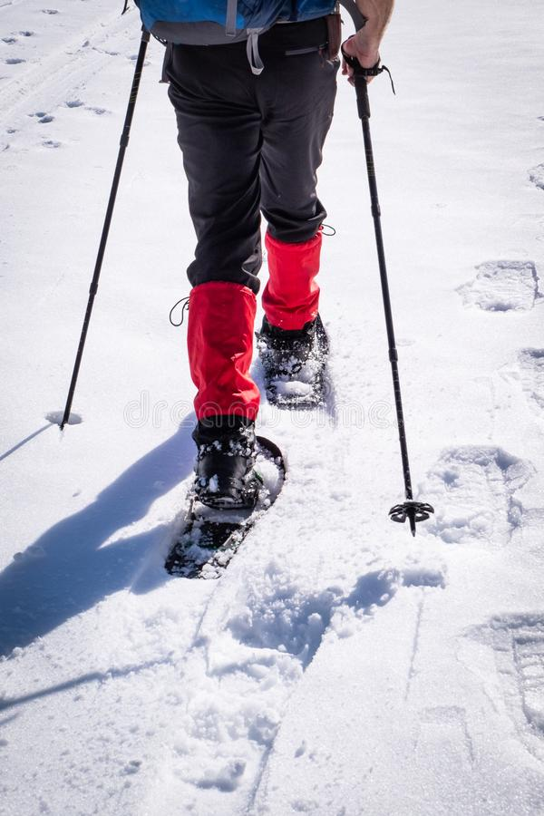 Detail of man hiking with snowshoes through snow on winterday stock photos
