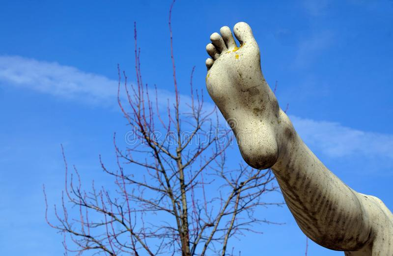Detail of a marble statue, depicting the foot. Blue background with tree. Foot fungus royalty free stock photography