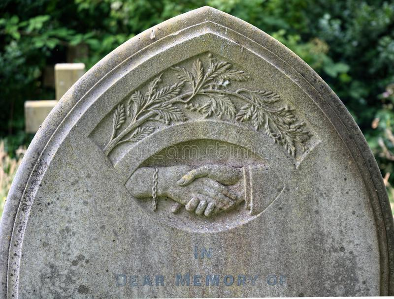 Memorial headstone. Hand holding hand stock images