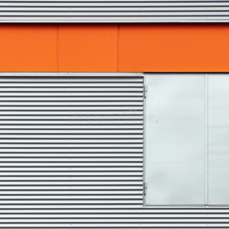 Detail of metal building. Architectural detail of horizontal metal siding with doors and an orange colored trim stock image
