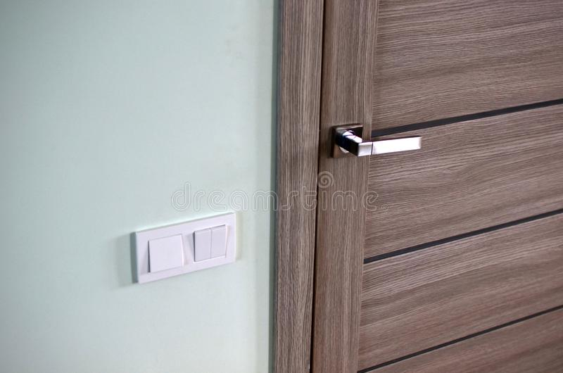 Detail of a metal handle on a wooden door in a house or apartment. Part of a chrome handle on a modern interior door. royalty free stock image