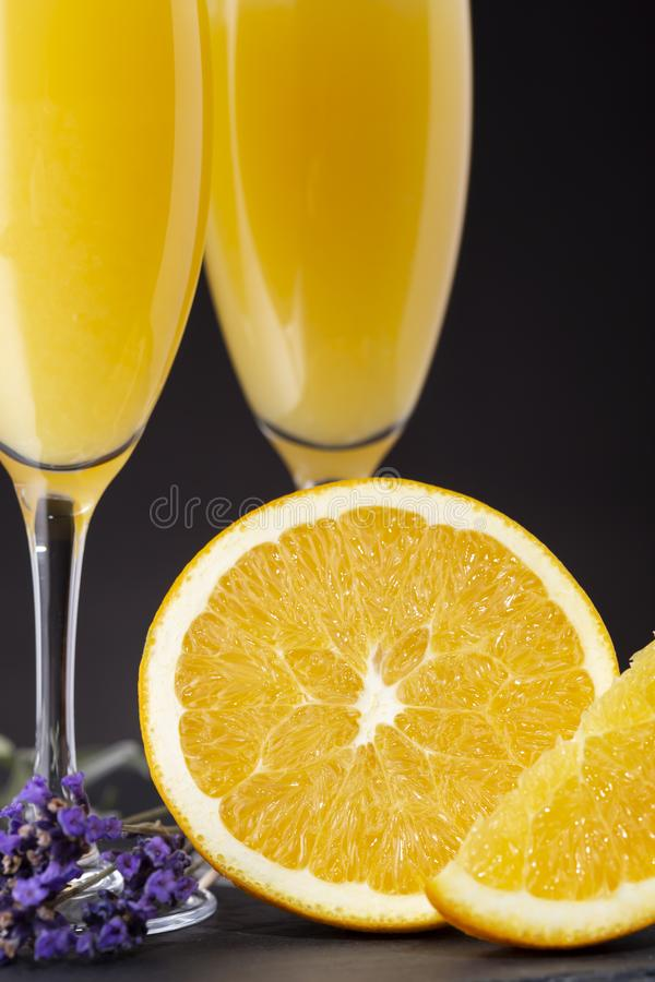 Detail of mimosa cocktails. In champagne glasses with orange juice and sparkling wine decorated with lavender leaves and orange slices. Selective focus on the stock photography