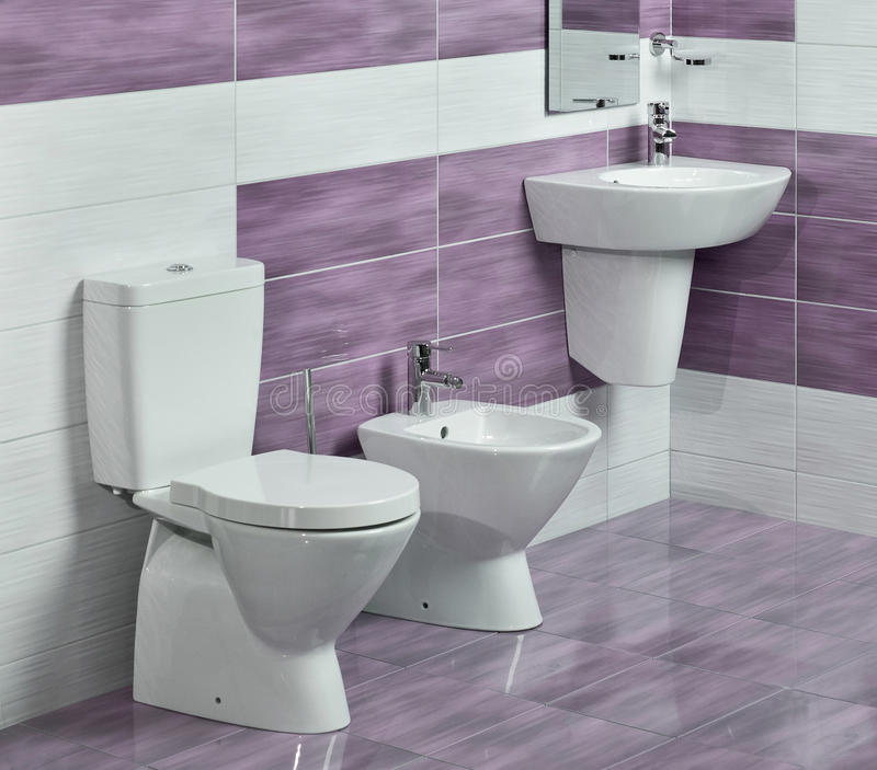 Detail of modern bathroom with sink, toilet and bidet. With purple and white tiles and miror stock images