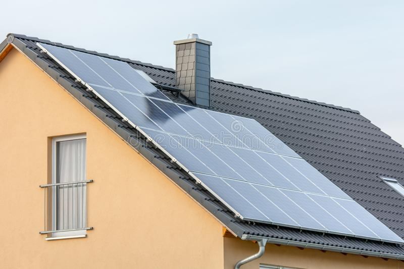 Photovoltaic system on residential building seen from a public road royalty free stock images