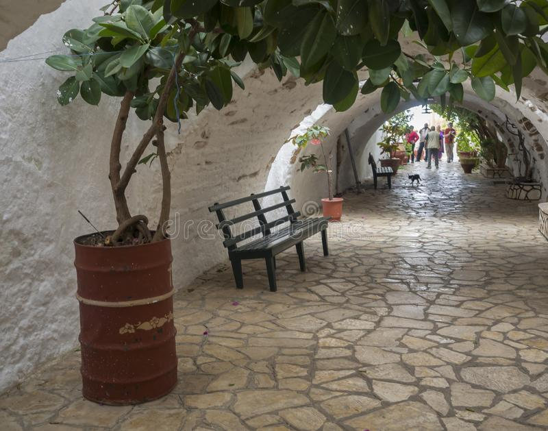 Detail from the Monastery of Paleokastritsa - Nice arcade with flower pots, bench and visiting tourist people, Corfu, Greece stock photography