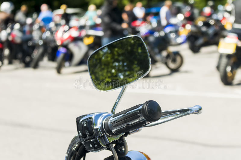 Detail on a motorcycle handlebar with mirror. Showing reflection of trees stock image