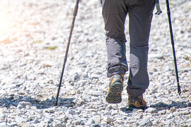 Detail of mountain walker on stony road with Nordic walking sticks.  stock image