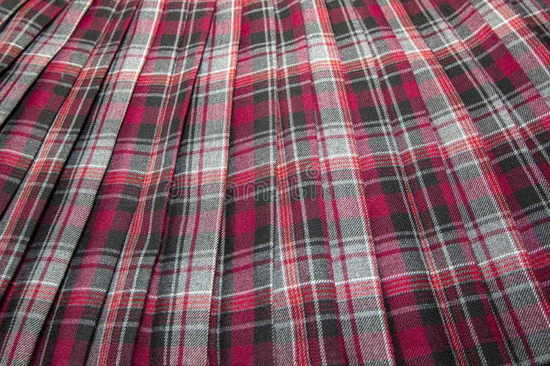 Detail of new fashion plaid pleated skirt: red, maroon, gray tartan school uniform fabric cotton/woolen material royalty free stock image