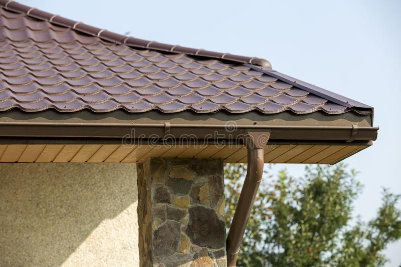 Detail of new modern house cottage corner with stucco walls decorated with natural stones, brown shingled roof and rain gutter pip stock photography