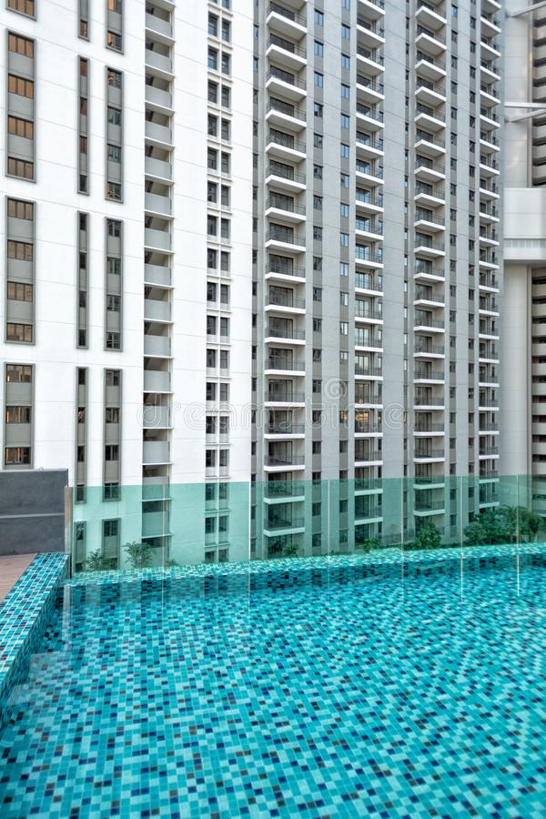 Detail of new residential apartment block, not yet occupied, with swimming pool in foreground. In George Town on Penang Island, Malaysia royalty free stock photography