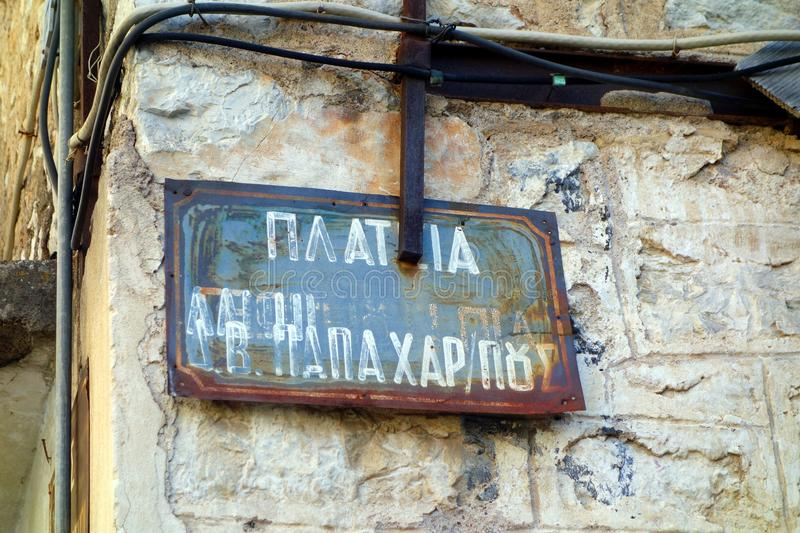 Rusted and Faded Street Sign on Old Building, Nafpaktos, Greece. Detail of an old and abandoned stone house in central Nafpaktos, Greece, with a rusted and faded stock photo