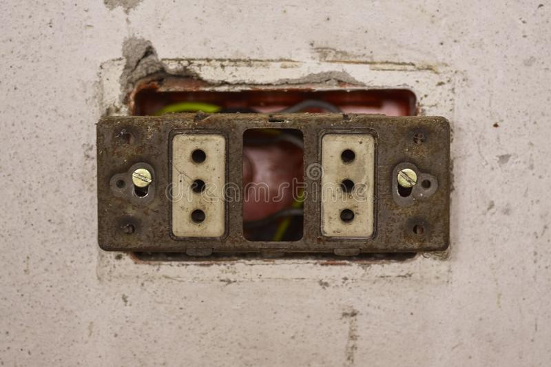 Absolutely unsafe electrical socket. Detail of an old broken and absolutely unsafe electrical socket royalty free stock image