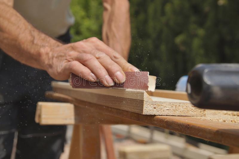 Male worker hands smoothing wood board using sandpaper. Sanding wood plank. royalty free stock photos