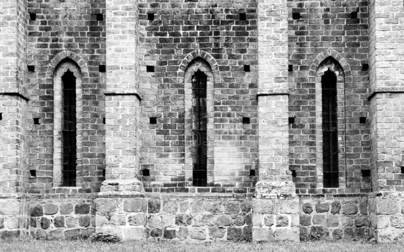 Detail of old cathedral monastery with medieval stone brick wall and elongated windows in characteristic brick gothic architecture. Style. Photo in black and royalty free stock images